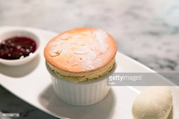 Platters of almond and vanilla souffle dessert with ice cream and red berry sauce