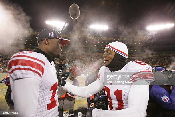 Plaxico Burress and Amani Toomer of the New York Giants congratulate each other following a game against the Green Bay Packers on January 20 2008 at...