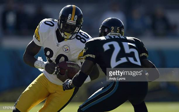 Plaxico Burress of the Pittsburgh Steelers carries the ball against Fernando Bryant of the Jacksonville Jaguars during the NFL game on December 1...