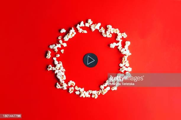play button and popcorn on a red background. - film oder fernsehvorführung stock-fotos und bilder