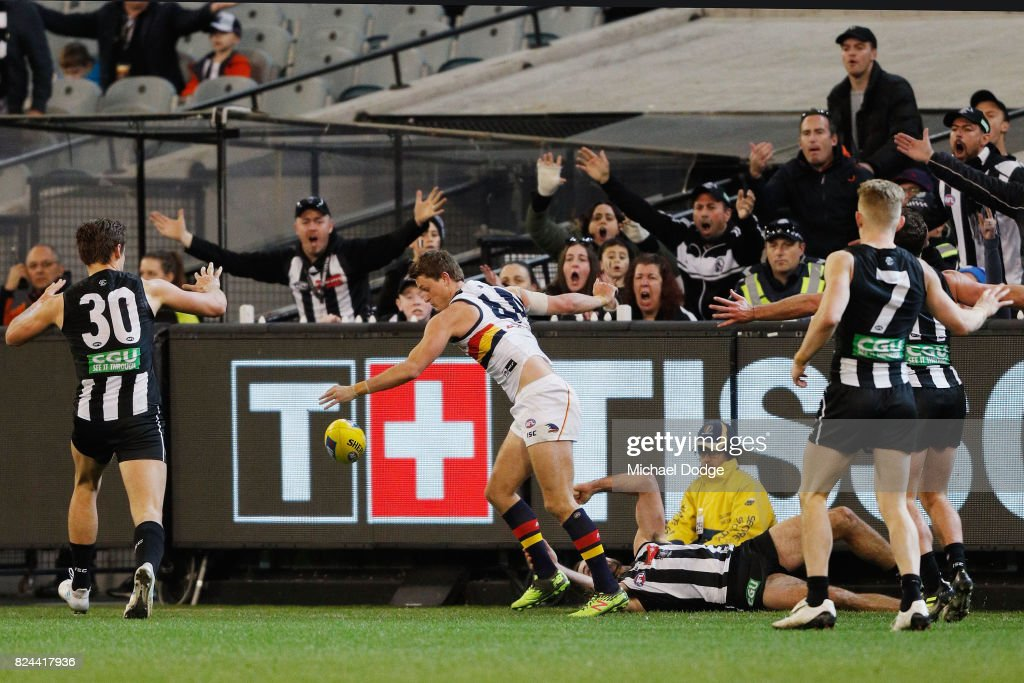 Play goes on after Matt Crouch of the Crows is tackled by Steele Sidebottom of the Magpies in the dying stages during the round 19 AFL match between the Collingwood Magpies and the Adelaide Crows at Melbourne Cricket Ground on July 30, 2017 in Melbourne, Australia.