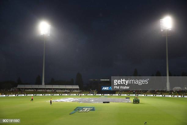 Play is postponed due to rain as the covers sit on the pitch during game two of the Twenty20 Series between New Zealand and the West Indies at Bay...