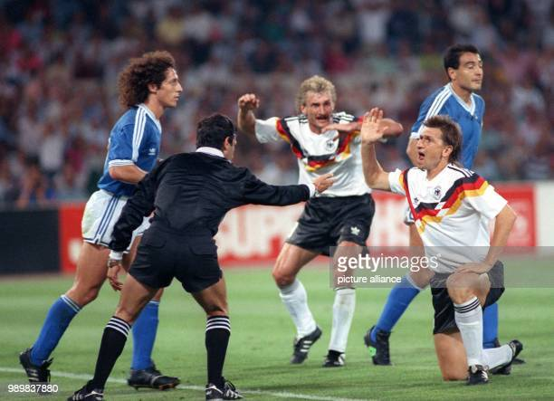 'Play On' signals Mexican referee Edgardo Codesal Mendez despite protests from German players Rudi Voeller and Klaus Augenthaler Argentineans Pedro...