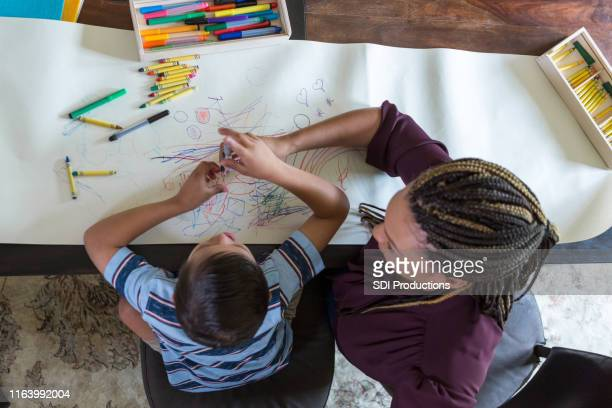play therapist colors with boy with down syndrome - alternative therapy stock pictures, royalty-free photos & images