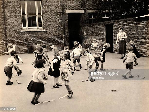 Play time at St Mary's school in Boston Lincolnshire with a teacher watching the children playing games during a break circa 1953