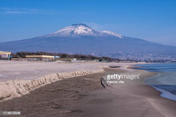 Playa beach empty on Easter Monday with in the background the volcano mountain Etna still with snow on April 13 2020 in Catania Italy Easter...