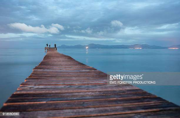 Playa de Muro with idyllic long wooden jetty in Caribbean coloured waters and mountain range in background and 3 people fishing.