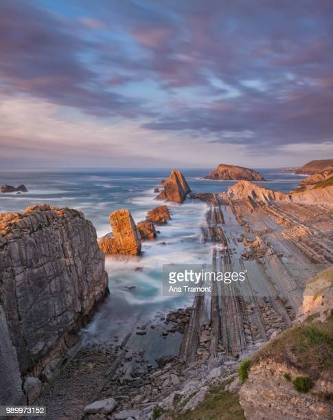 playa del portio rocky beach at sunset, liencres, cantabria, spain - カンタブリア ストックフォトと画像