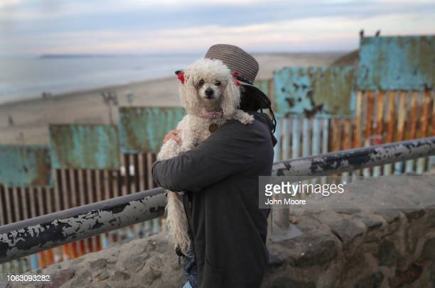 Playas de Tijuana resident Juantia Leon holds her poodle Mini while taking in the view of the Pacific Ocean next to the USMexico border fence on...