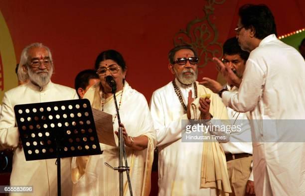 Playback singer Lata Mangeshkar flanked by historian Babasaheb Purandare and Shiv Sena chief Bal Thackeray during the Senas celebrations at the...