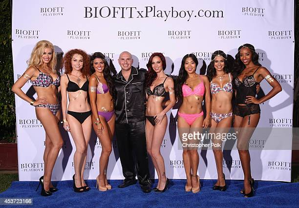 Playboy brand partner Pitbull poses with Playmates Kennedy Summers Scarlett Keegan Val Keil Jaime Edmondson Hiromi Oshima Raquel Pomplun and...