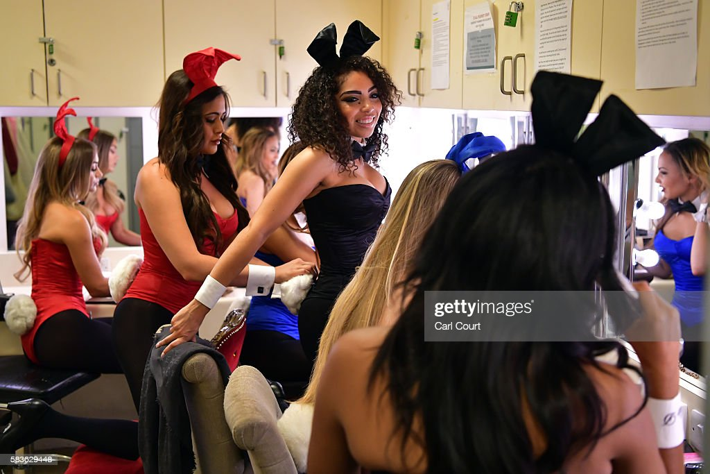A Playboy Bunny affixes a tail onto her colleagues costume as they prepare themselves before starting work at the Playboy Club on July 26, 2016 in London, England. The Playboy Club London is celebrating its 50th anniversary this year and will mark the event with a 'Touch of Gold' party on July 29.