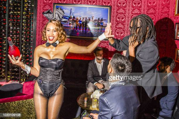 A Playboy Bunny high fives a guest during the grand opening of the Playboy Club in New York US on Wednesday Sept 12 2018 The opening ofthe...