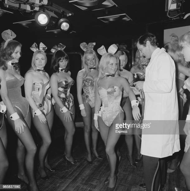 Playboy Bunny waitresses line up to receive a flu vaccine from a medic dressed in a white coat at the Playboy Club in London on 10th October 1972
