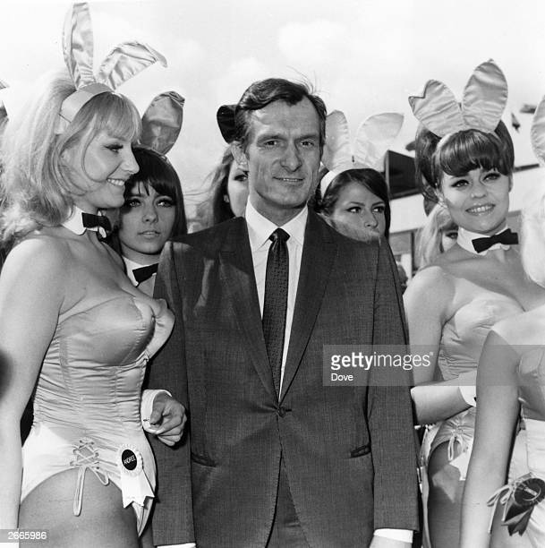 Playboy editor and tycoon Hugh Hefner is greeted by a group of bunny girls from his Playboy Clubs upon his arrival at London Airport