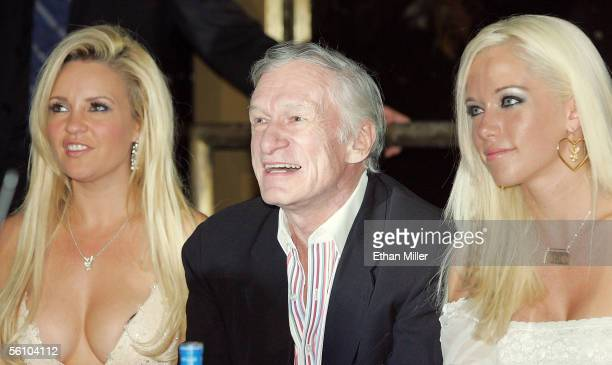 Playboy founder and EditorinChief Hugh Hefner and two of his girlfriends Bridget Marquardt and Kendra Wilkinson watch a fashion show to introduce...