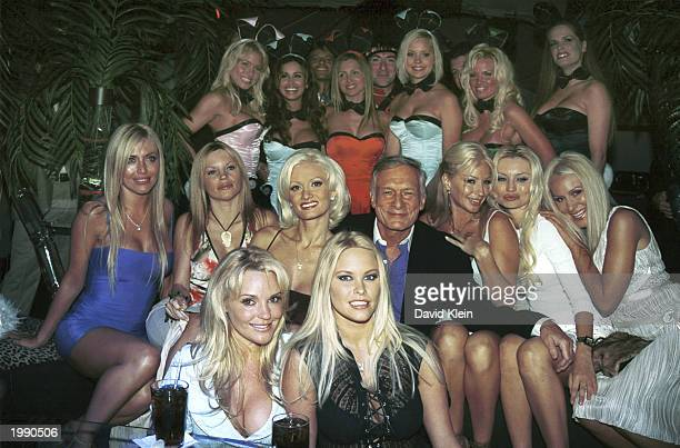 Playboy founder Hugh Hefner and playmates pose in front of the touring Playmates and the Dewar's Highlander on May 8 2003 in Bel Air California The...