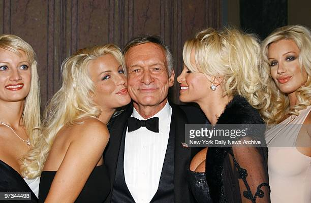 Playboy founder Hugh Hefner is smooched by playmates during a New York Friars Club roast of Hefner at the New York Hilton