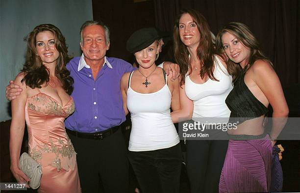 Playboy founder Hugh Hefner poses with model Carrie Stevesn actress Jaime Bergman and unidentified models during the Tongue Magazine Fall 2002 Issue...