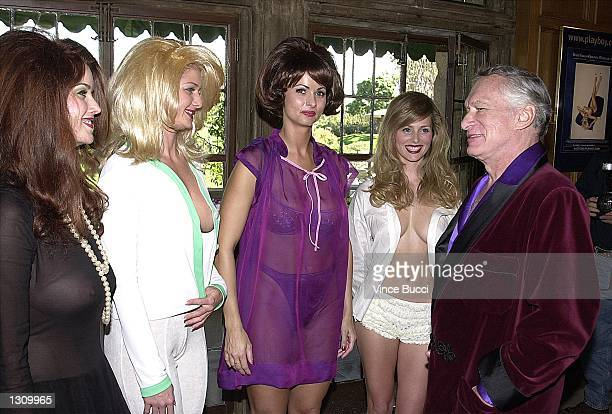 Playboy founder Hugh Hefner right talks with playmates left to right Carrie Stevens Kalin Olson Karen McDougal and Deanna Brooks dressed as pinup...