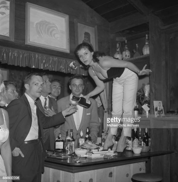 Playboy Magazine founder and publisher Hugh Hefner attends a party in his honor as actress Joan Bradshaw pours him a drink on June 26 1957 in Los...