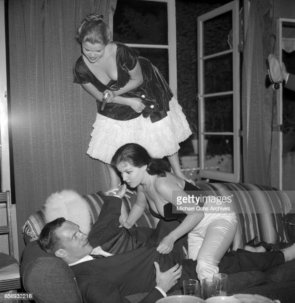 Playboy Magazine founder and publisher Hugh Hefner attends a party in his honor with actresses Joan Bradshaw and Susanne Sidney on June 26 1957 in...