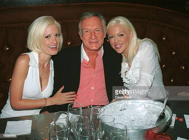 Playboy models Holly Madison and Tiffany Holiday hug their boyfriend Hugh Hefner during a birthday dinner party for Hef's two other girlfriends...