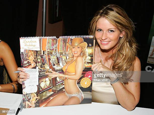 Playboy Playmate Sandra Hubby poses with her photo in Playboy's 2006 'Playmates in Las Vegas' calendar at the fourth anniversary celebration of the...