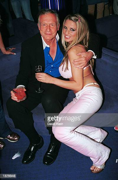 Playboy publisher Hugh Hefner poses with playmate Jordan outside The Standard Hotel August 1 2002 in West Hollywood California