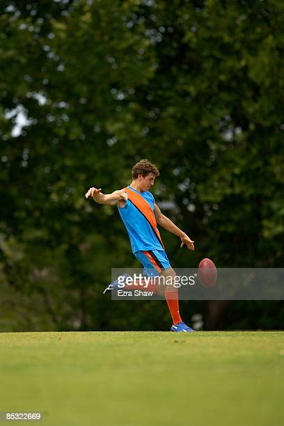 player about to kick an australian football - kicking stock pictures, royalty-free photos & images
