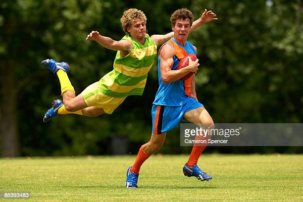 player about to tackle opposition in football game - australian rules football stock-fotos und bilder