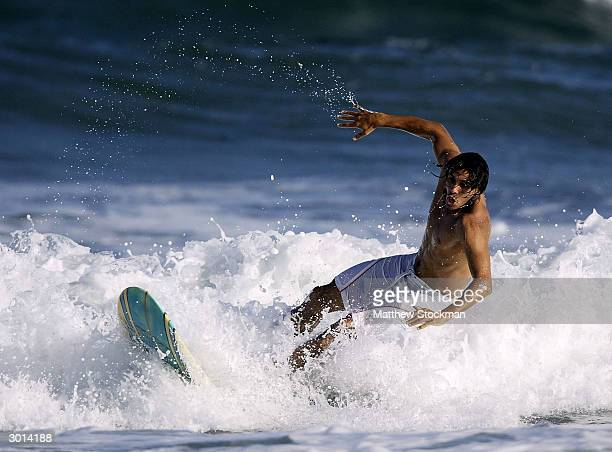 ATP player and novice surfer Mariano Zabaleta of Argentina hits the waves during the Brasil Open on February 25 2004 in Costa Do Sauipe Bahia Brazil