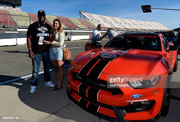 Player Antwione Williams of the Detroit Lions and guest pose with the pace car before the NASCAR Sprint Cup Series FireKeepers Casino 400 at Michigan...