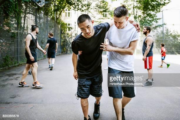 player assisting his injured teammate during urban basketball game. - unterstützung stock-fotos und bilder