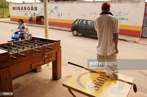A player at Japeri Municipal Public Golf Course takes a brake from playing at a bar a few feet from the course May 14 2003 in Rio de Janeiro suburb...