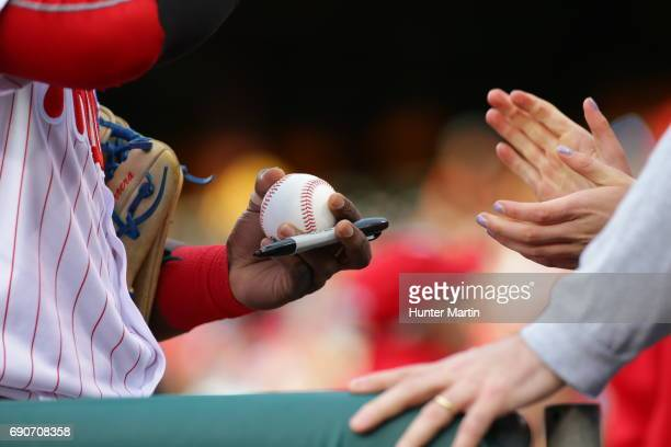 A player autographs a baseball for a fan before a game between the Seattle Mariners and the Philadelphia Phillies at Citizens Bank Park on May 9 2017...