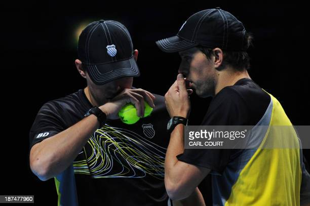 US player Bob Bryan and his partner US player Mike Bryan talk between points against Poland's Marcin Matkowski and his partner Poland's Mariusz...