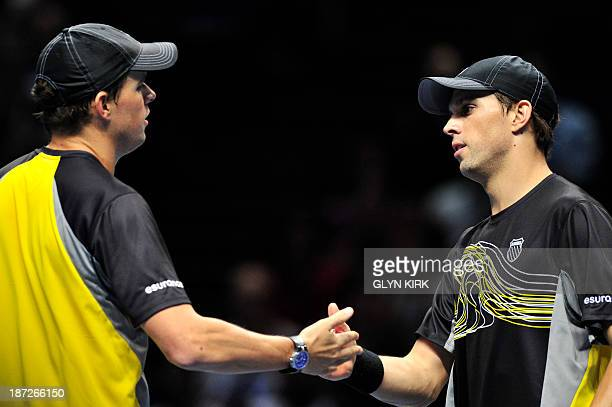 US player Bob Bryan and his partner US player Mike Bryan touch hands between points against Pakistan's AisamUlHaq Qureshi and his partner...