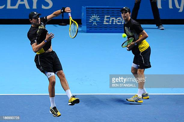 US player Bob Bryan hits a return as his partner US player Mike Bryan stands ready against Croatia's Ivan Dodig and his partner Brazil's Marcelo Melo...