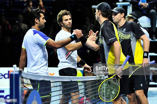 US player Bob Bryan stands by as his partner US player Mike Bryan shake hands at the net with Pakistan's AisamUlHaq Qureshi and his partner...