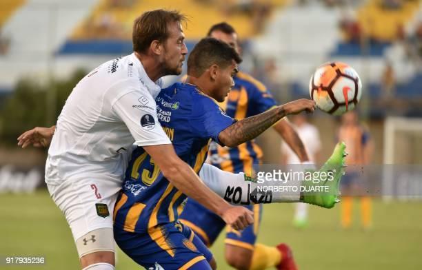 Player Brian Cucco of Ecuador's Deportivo Cuenca vies for the ball with Blas Armoa of Paraguay's Sportivo Luqueno during their Copa Sudamericana...
