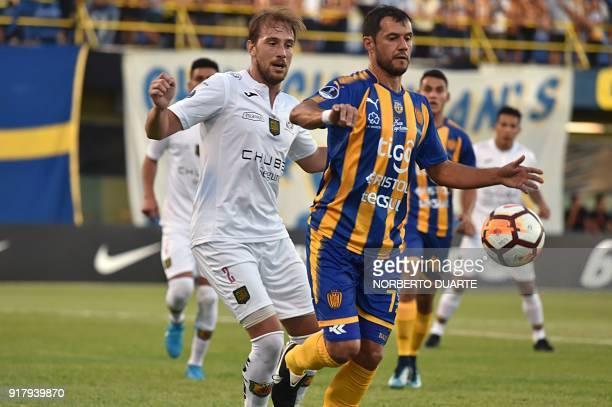 Player Brian Cucco of Ecuador's Deportivo Cuenca vies for the ball with Fredy Bareiro of Sportivo Luqueno of Paraguay during their Copa Sudamericana...