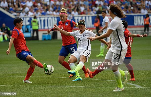 USA player Carli Llyod has a shot blocked by South Korea's Kim Sooyun during a friendly match between the USA and South Korea at Red Bulls Arena in...