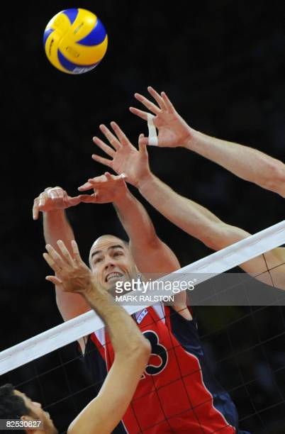 US player Clayton Stanley spikes the ball past Brazil's Dante Amaral and Andre Heller during the men's volleyball gold medal match in the 2008...