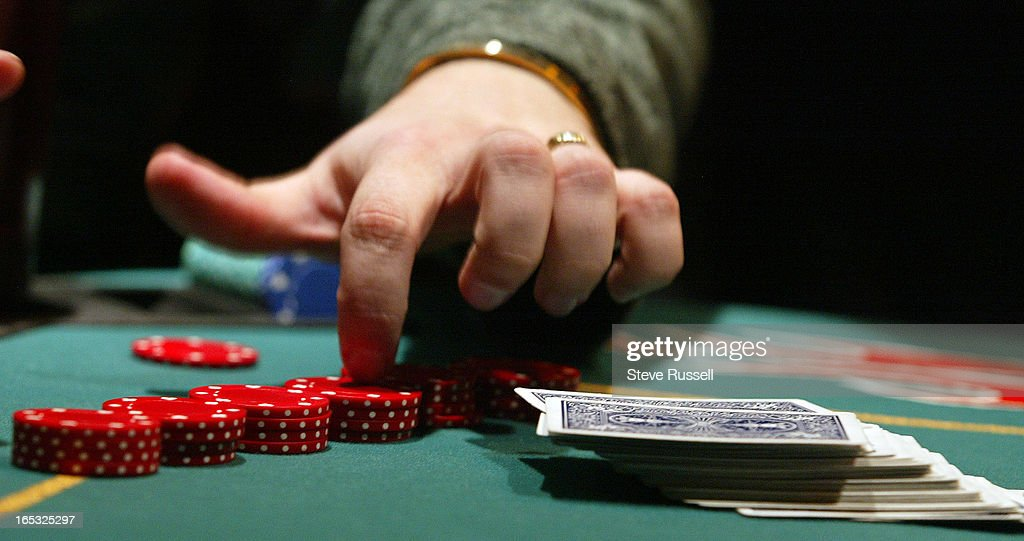 TEXAS HOLD 'EM POKER---03/07/05---A player counts his chips while placing a bet, the popularity of T : News Photo