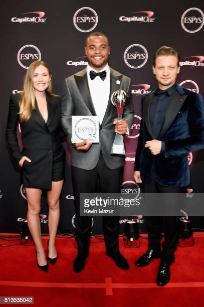 NFL player Dak Prescott winner of the Best Breakthrough Athlete award with actors Elizabeth Olsen and Jeremy Renner attend The 2017 ESPYS at...