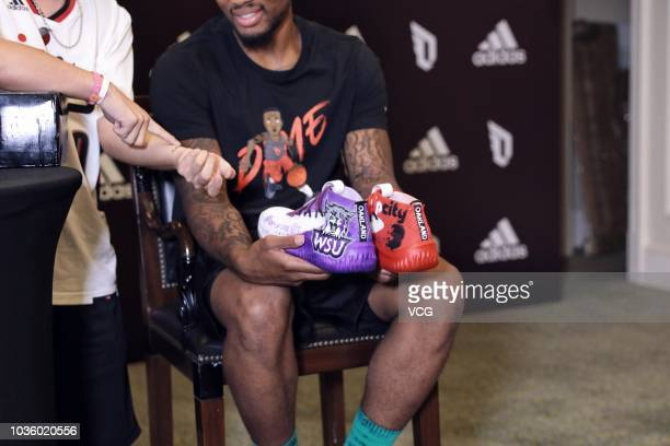 NBA player Damian Lillard of the Portland Trail Blazers holds shoes in his hands at an Adidas press conference during his China tour on September 11...
