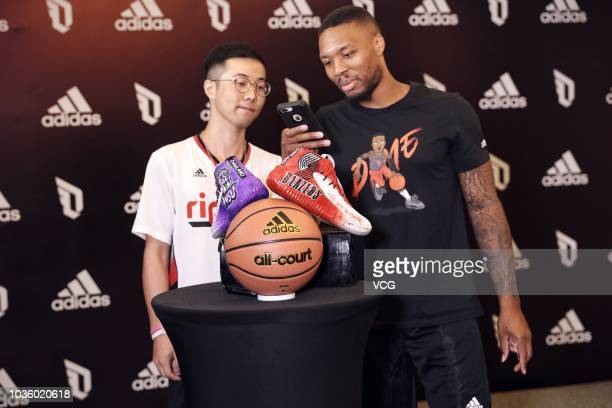 NBA player Damian Lillard of the Portland Trail Blazers takes pictures of shoes at an Adidas press conference during his China tour on September 11...