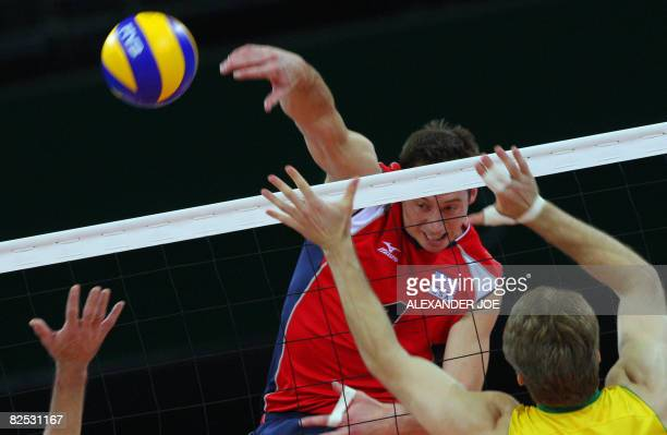 US player David Lee spikes the ball as Brazil's players attempt to block during the men's volleyball gold medal match in the 2008 Beijing Olympic...