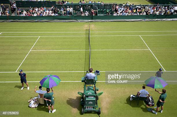 US player Denis Kudla and Japan's Kei Nishikori rest under umbrellas in between sets during their men's second round match on day four of the 2014...